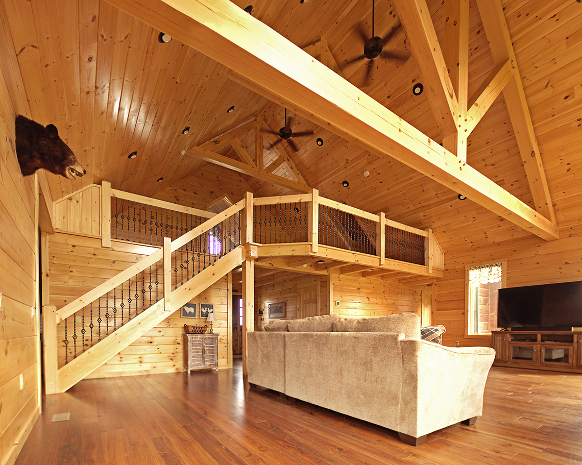 Interior family room with railings and timber trusses.